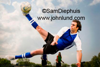 A man is in mid-air kicking a soccer ball. Action sports photo. The ball and the mans foot are over his head.